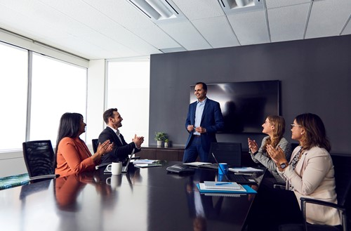 Employees clapping for manager in team meeting.
