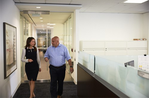Two employees walking down a corridor.