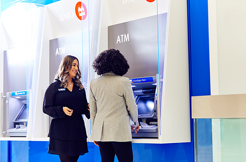 Female employee smiling to another female in front of ATM.