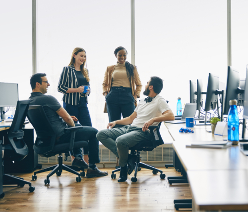 Group of employees having a discussion at their desks.