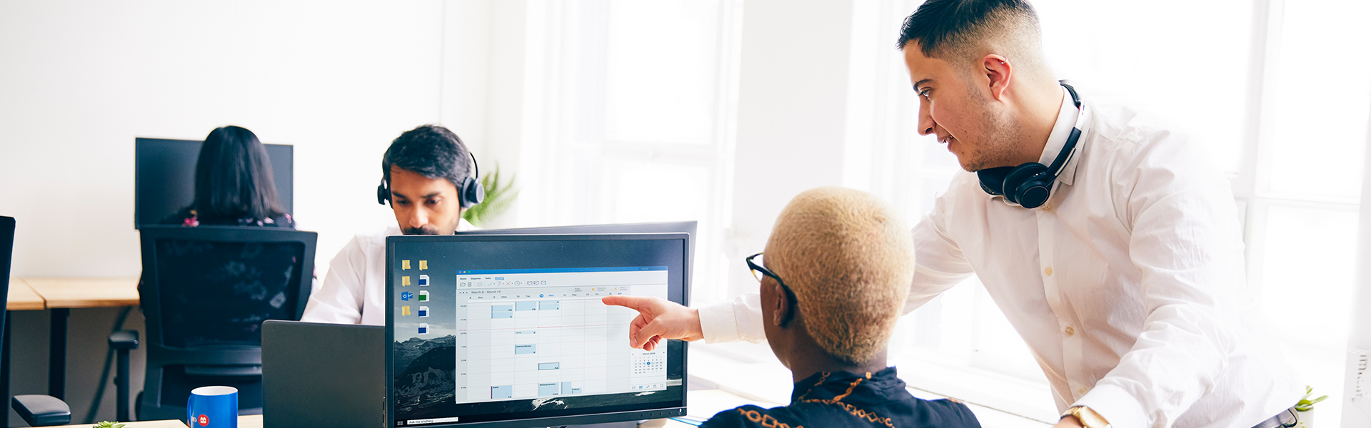 Male employee pointing at computer screen.