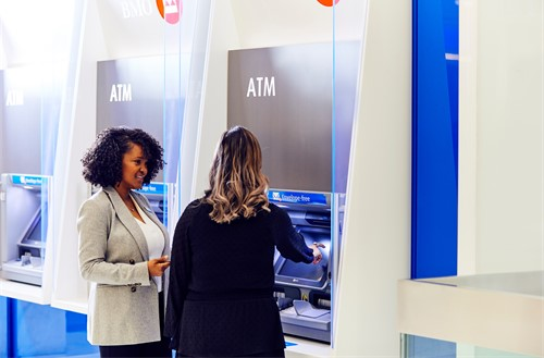 Two female employees standing at ATM.