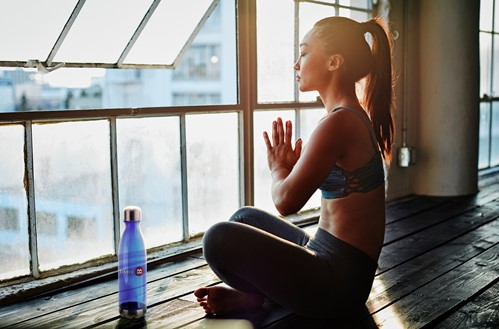 Woman meditating in front of large window.