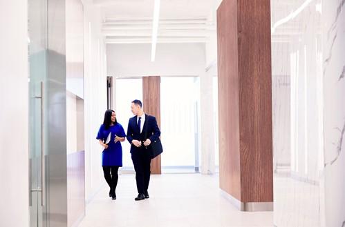 Deuxcollègues qui discutent en marchant dans un corridor.