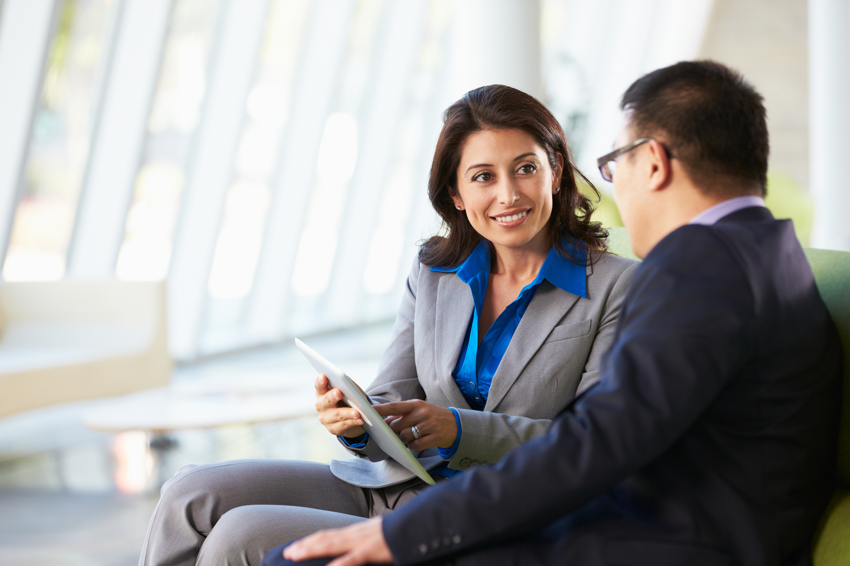 woman in suit with tablet looking at man in suit