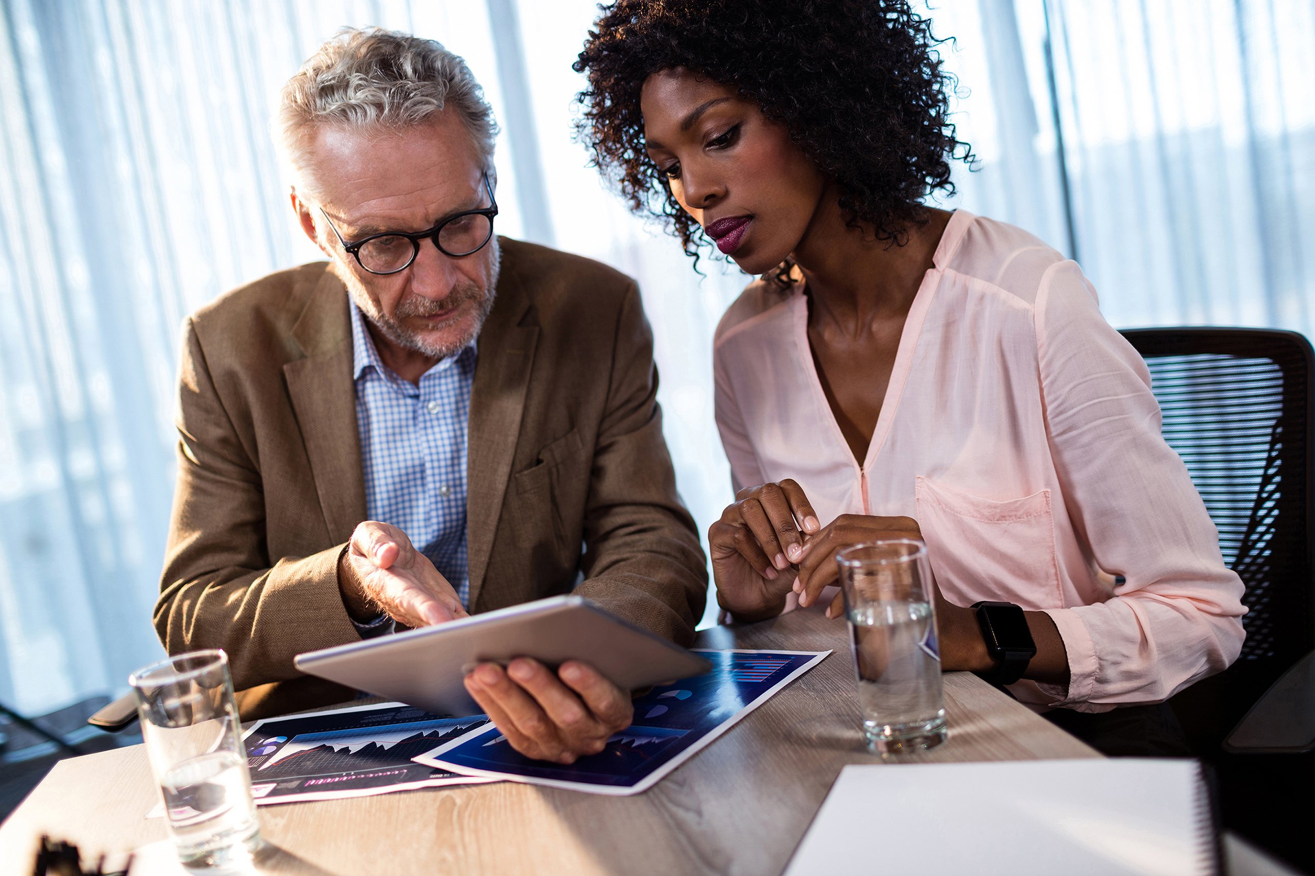 man points at tablet as woman next to him looks