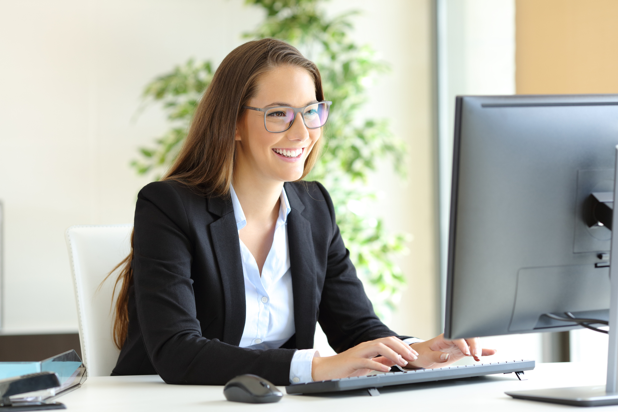 Professional woman sitting at desk typing and looking at screen.