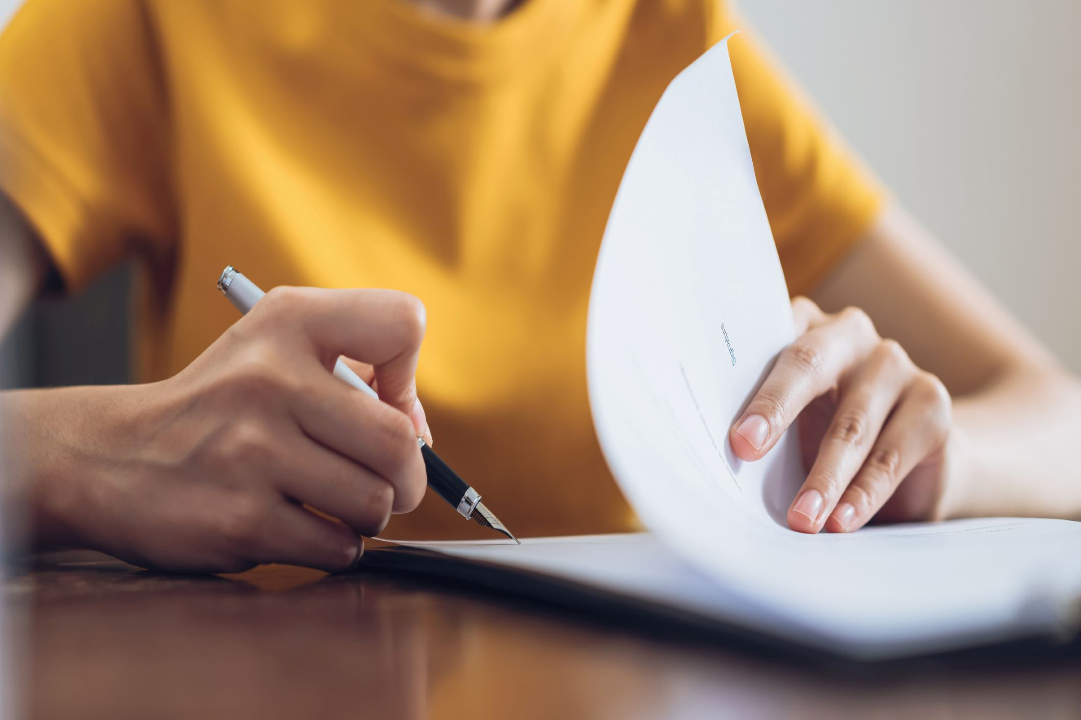 close up on a woman signing a document