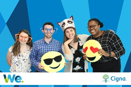 OLDP associates posing with emoji pillows, big glasses and cat props