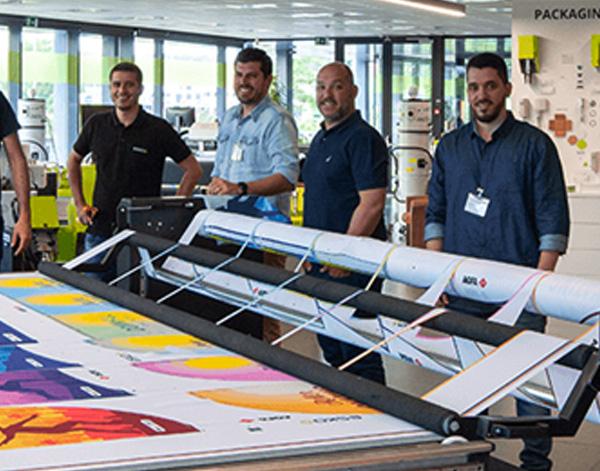 Photograph of ESKO associates near large format printer