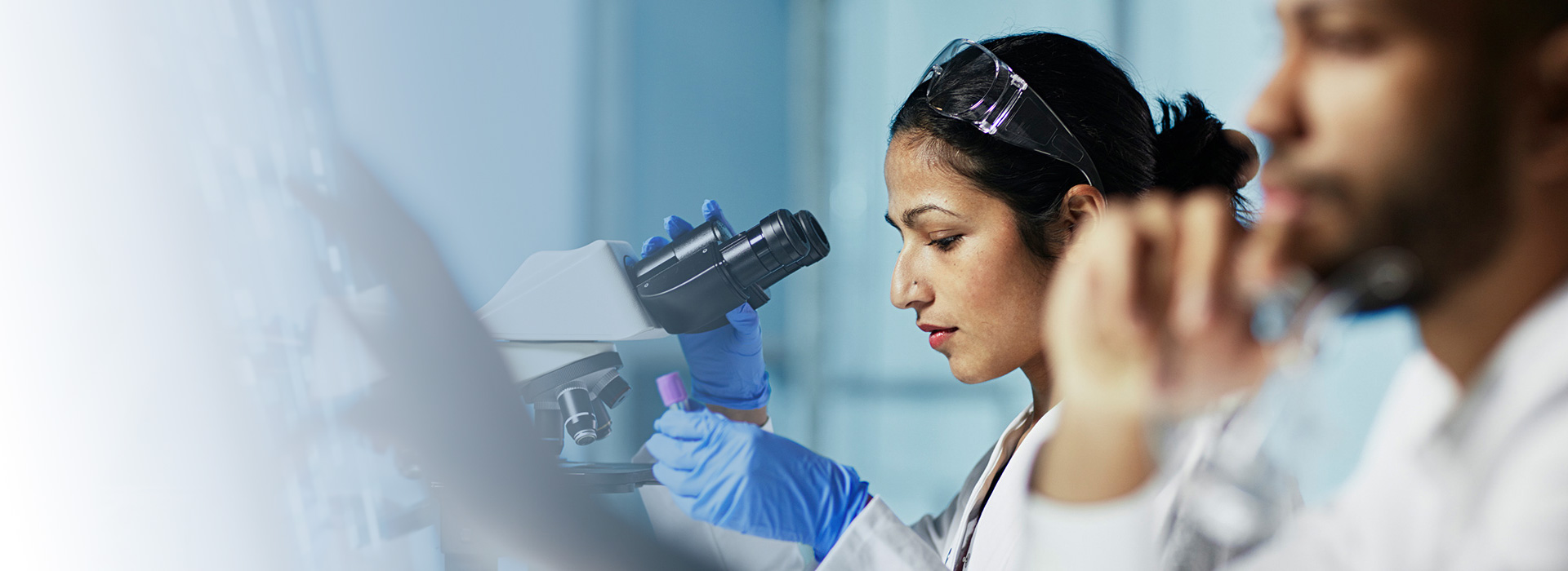 Photograph of Pall associate using microscope in lab