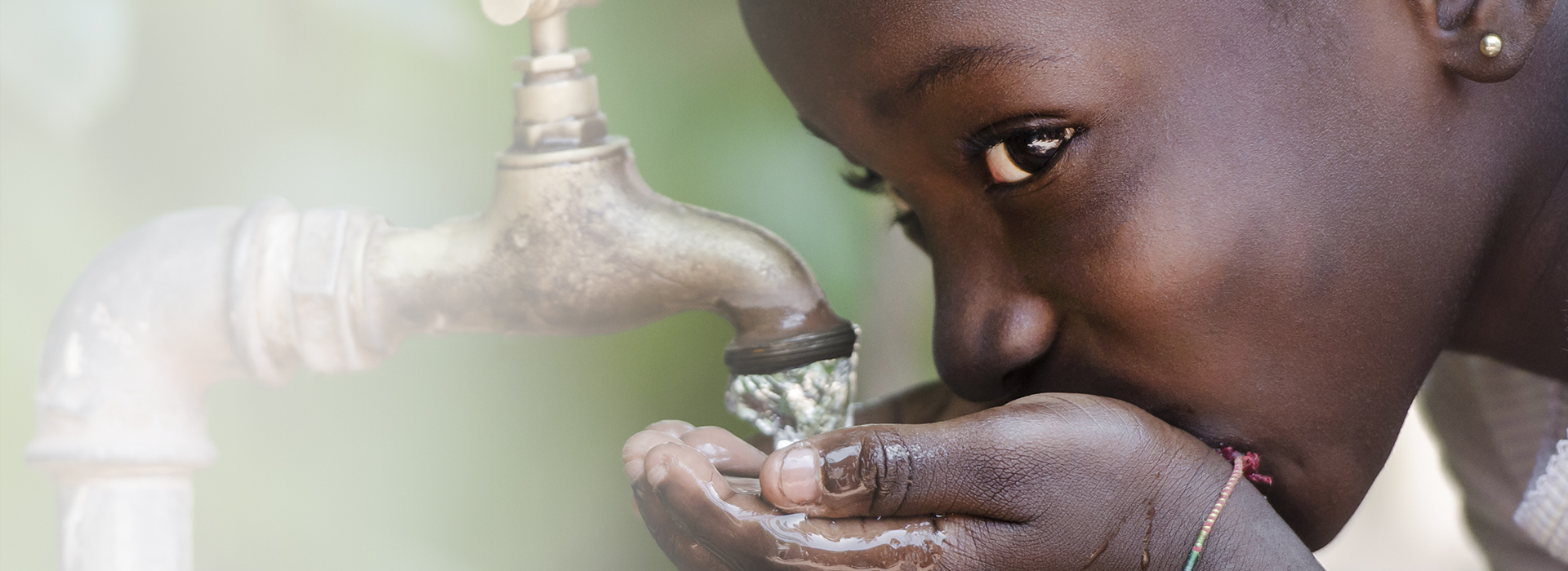 Young girl drinking water from faucet