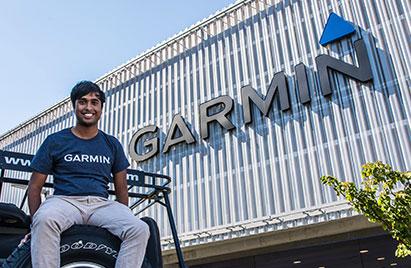 Garmin associate sitting on back of a Jeep in front of Garmin logo on parking garage