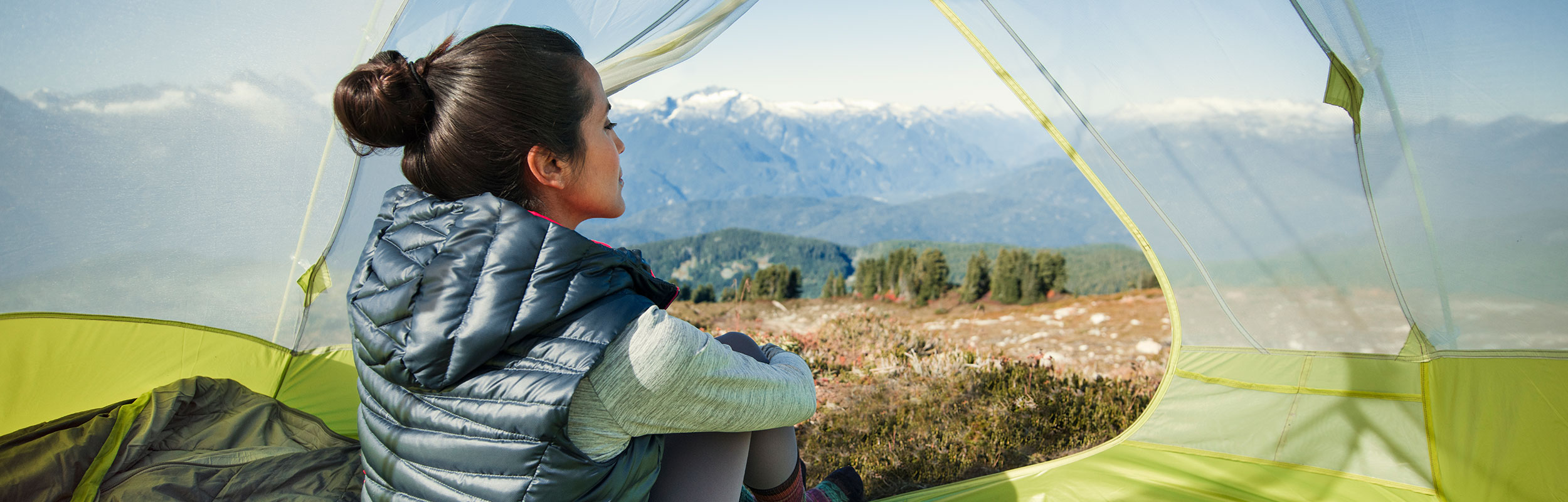 A woman looks at a view of mountains from inside a tent