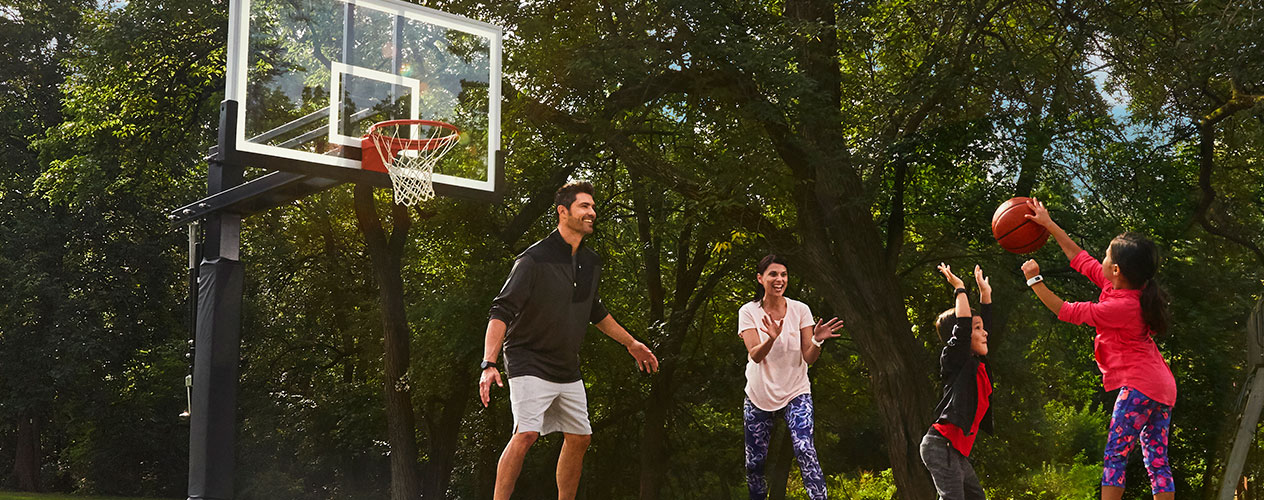 Two adults and two preteens play basketball