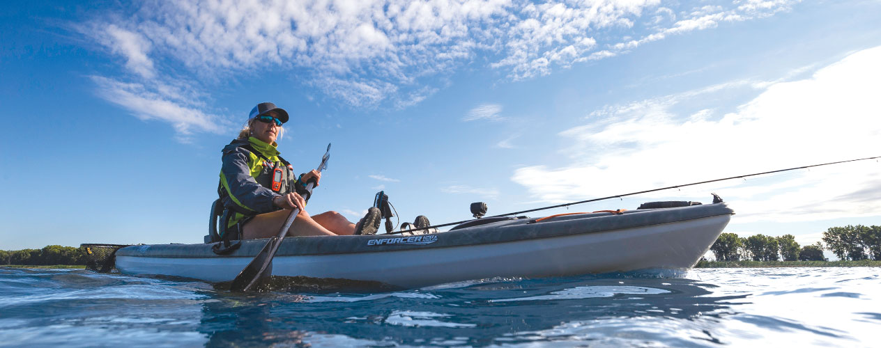 A kayaker uses a Garmin camera, wearable and navigation device while out on a freshwater lake