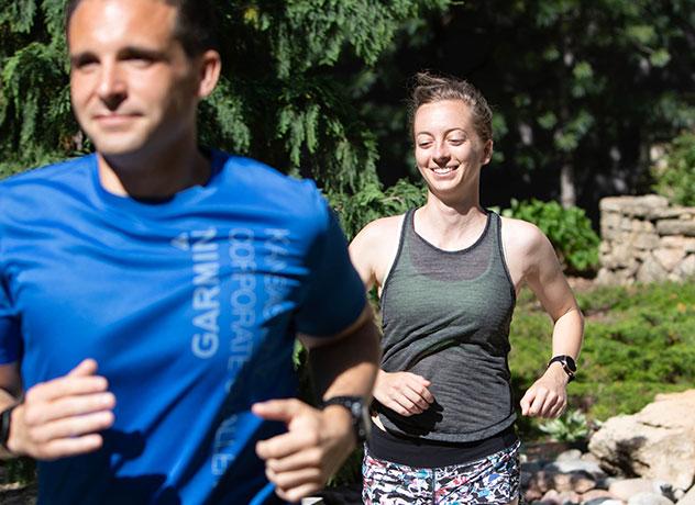 A smiling woman runs behind a man in a blue shirt
