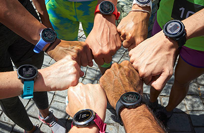 Hands touching each other in circle. All are wearing a Garmin wearable.