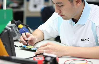 An electronics assembler solders a PCB at a Garmin manufacturing facility