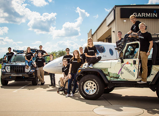 A small group of Garmin interns pose near the Garmin Jeep, another vehicle and a small plane