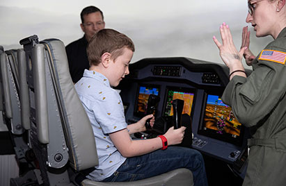 A Garmin associate wearing a flight suit explains how to use the flight simulator lab to a preteen boy
