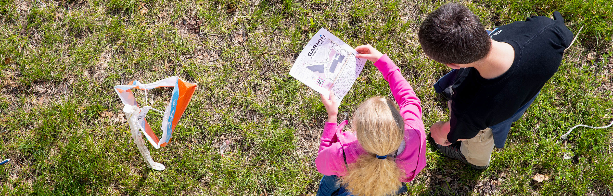 A bird'seye shot of a preteen boy and girl looking at a map for an orienteering challenge