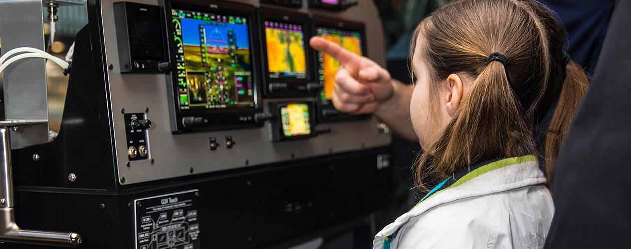 A young girl examines a Garmin aviation panel