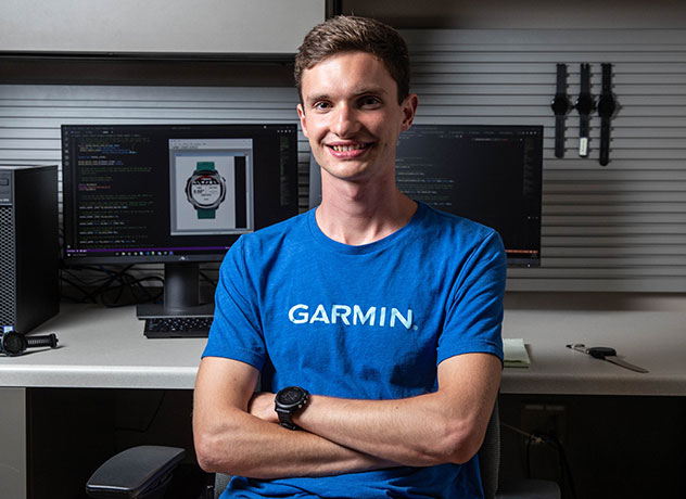 A Garmin intern stands in front of a workbench