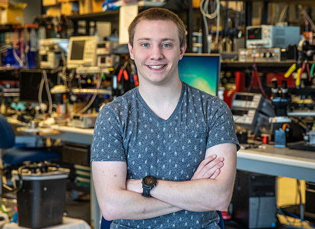 Garmin intern Nathan stands in front of his workbench