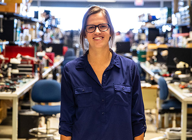 A young woman wearing glasses stands between two engineering workbenches