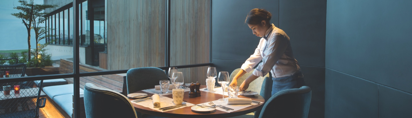 Food and Beverage Team Member setting a table in a hotel restaurant