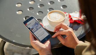 person with a coffee looking at a mobile phone