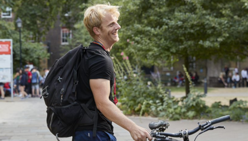 person standing with bike in Guy's campus quad