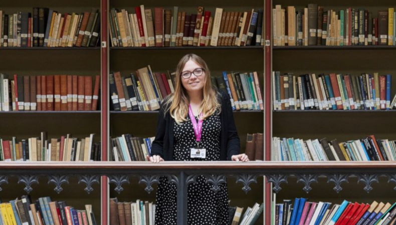 person standing in front of large book shelves