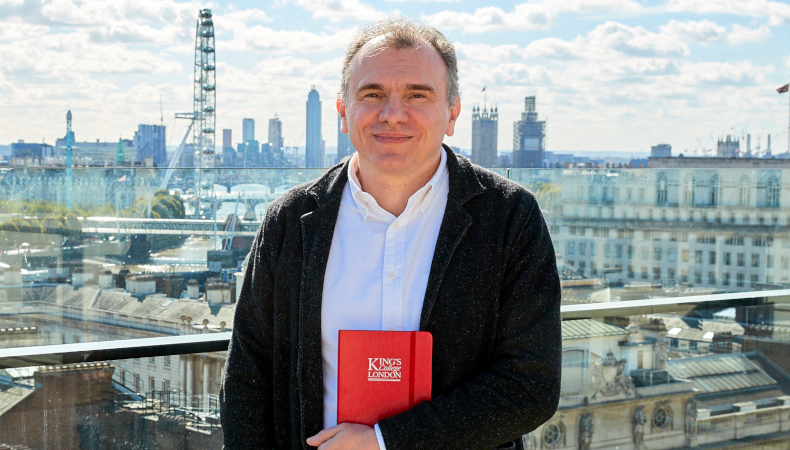 person holding a King's branded book with London skyline in the background