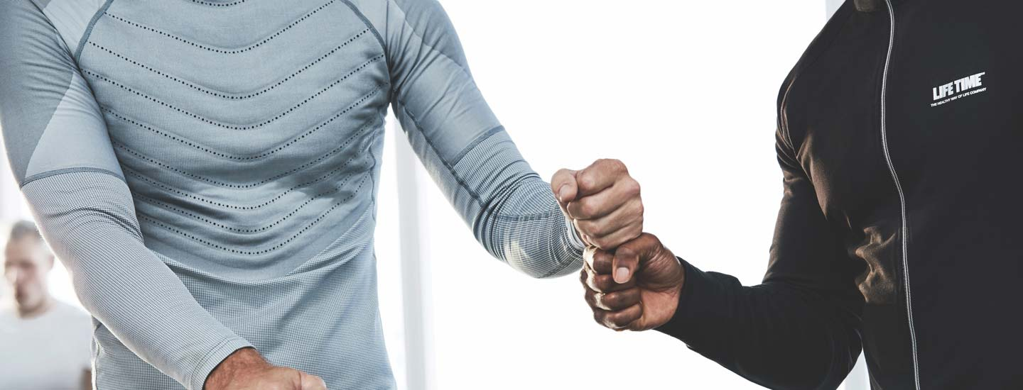 Trainer and member fist bumping.