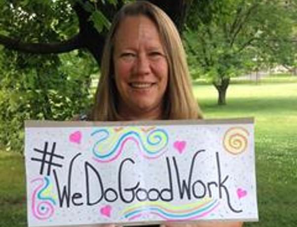 "Jane, a Magellan employee, holding a sign saying ""We do good work"""