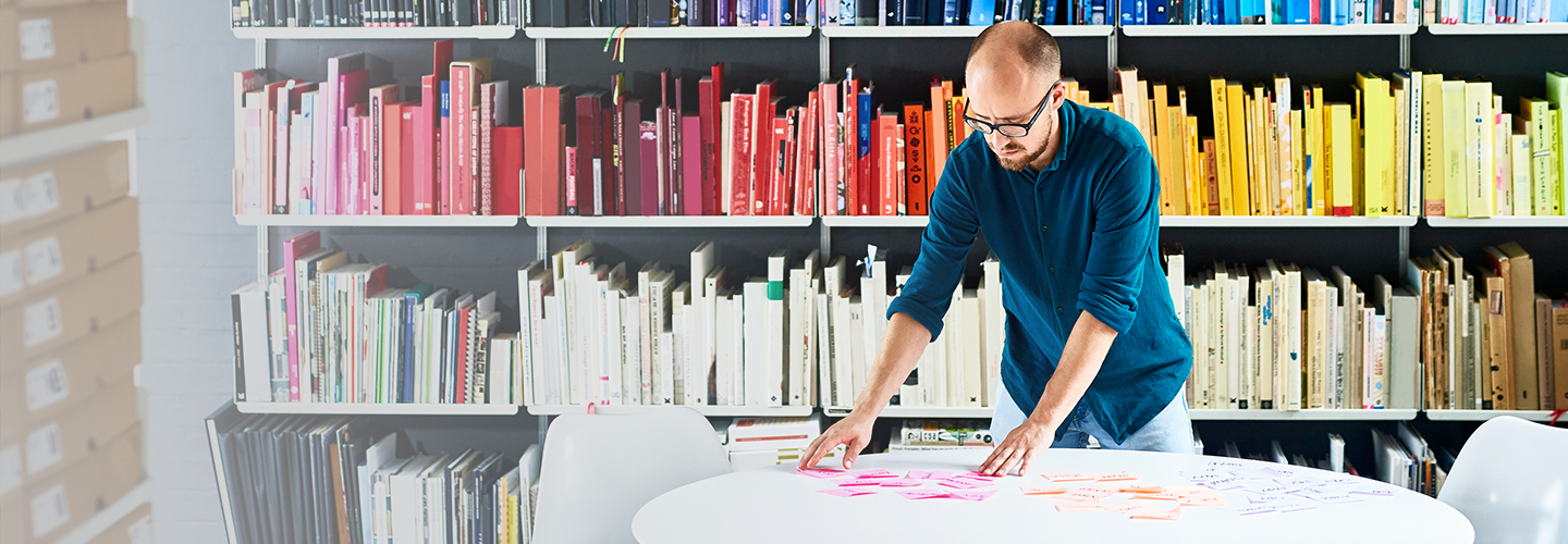 Man reviewing papers in front of shelves of books
