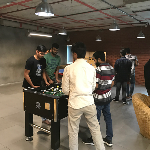Employees in the India office playing foosball