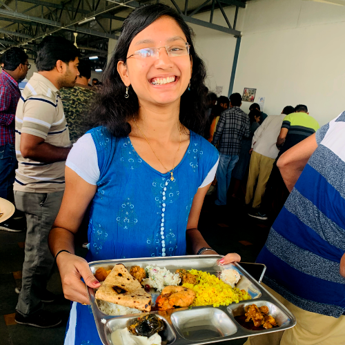 Employee at the pot luck in the India office enjoys her meal!