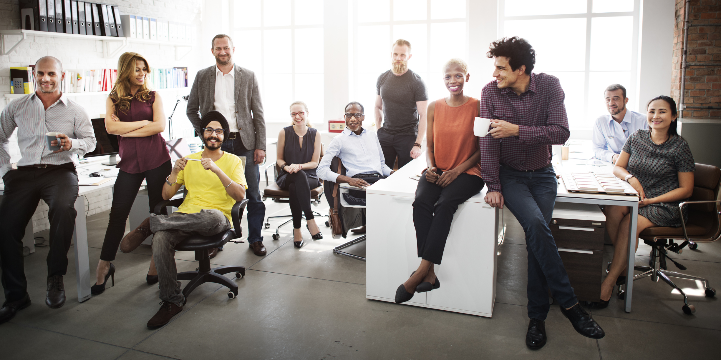 Group of coworkers sitting and standing in an office environment