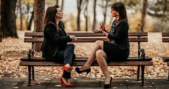 Two women using American Sign Language while sitting on park bench