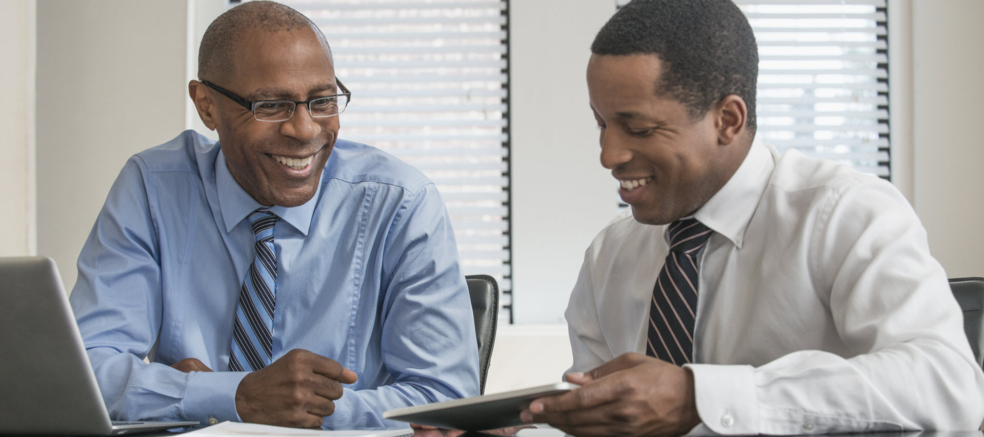 Two men meeting in an office reviewing data