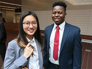 Two collegiate students smile for photo