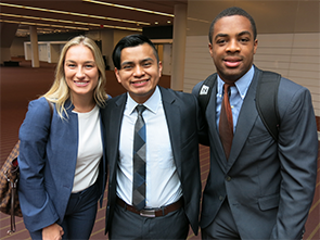 Three collegiate students stop to smile for picture