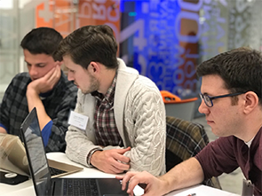 Collegiate men work together to solve a problem