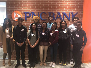 A group of high school students gather under a PNC sign