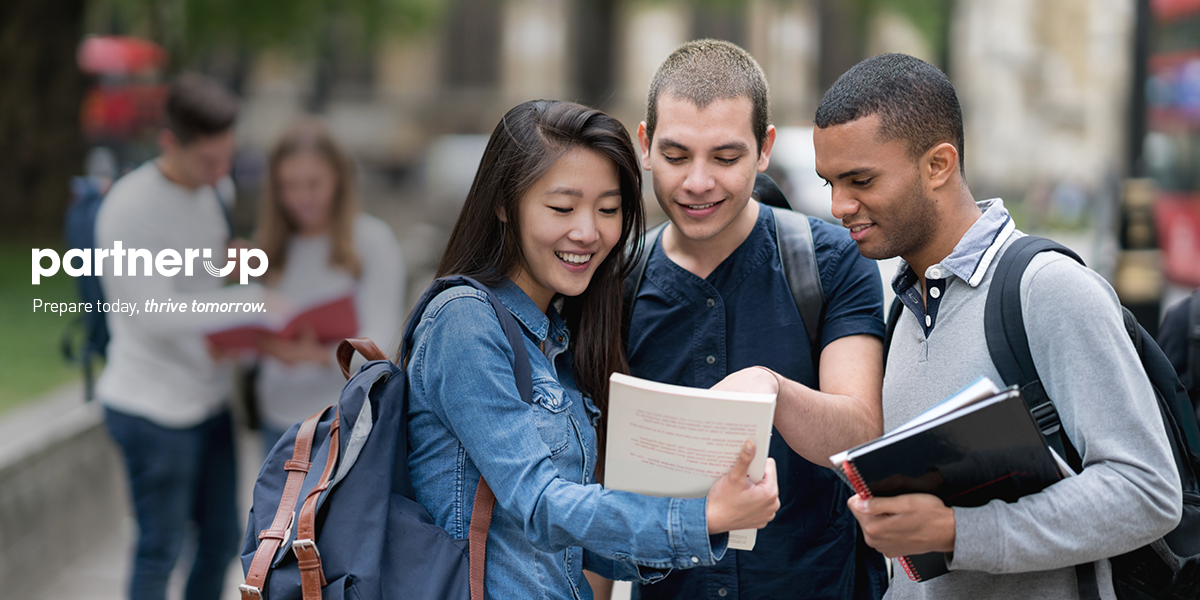 Three high school students looking at a book together