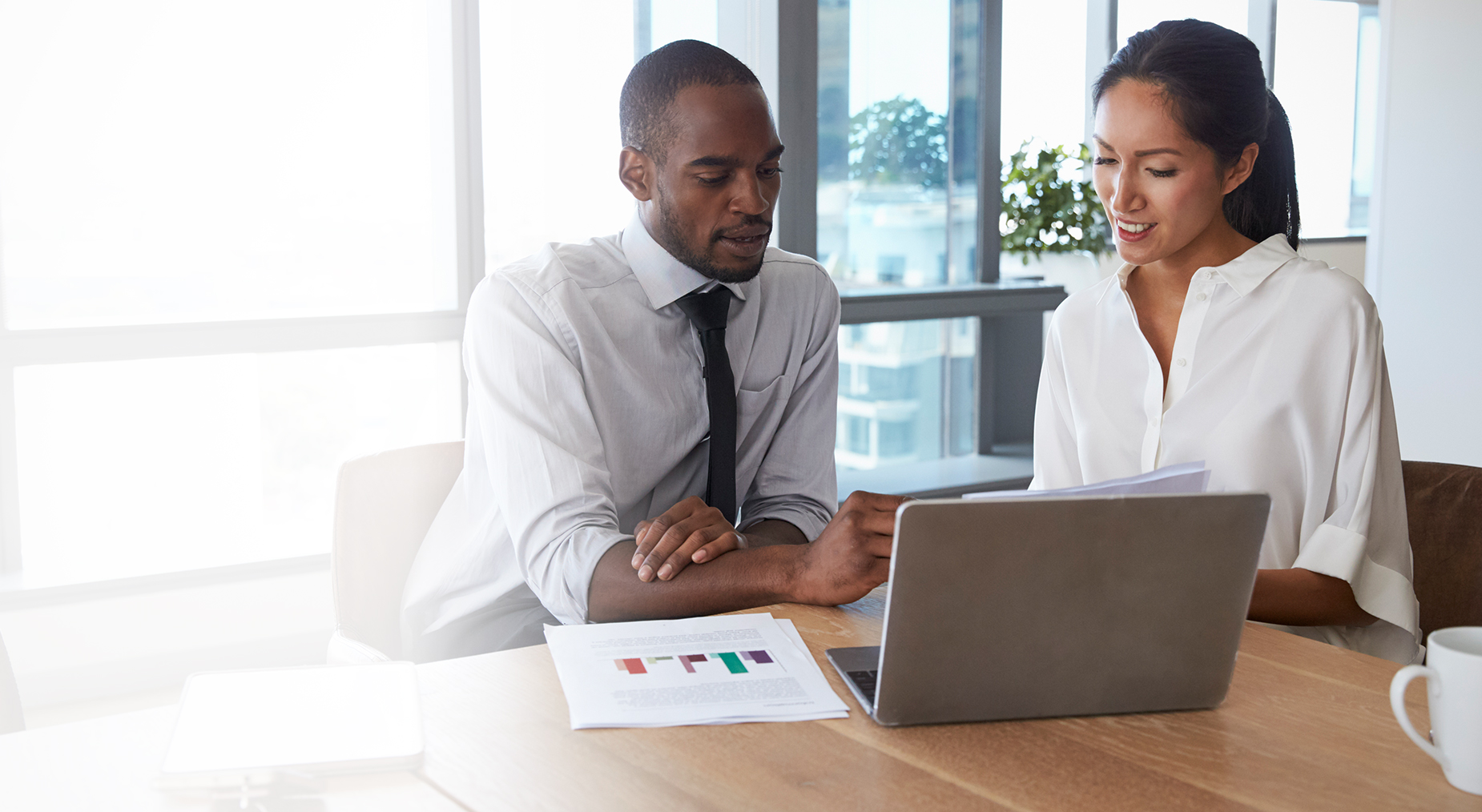Man and woman reviewing charts in front of laptop