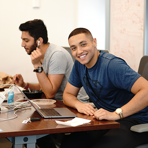Two young men sitting at a desk. One on the background with earbuds on, and another looking at the camera and smiling.